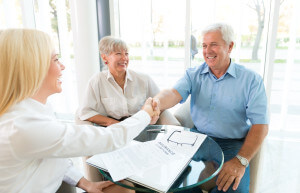 Senior Couple Shaking Hand With Insurance Agent